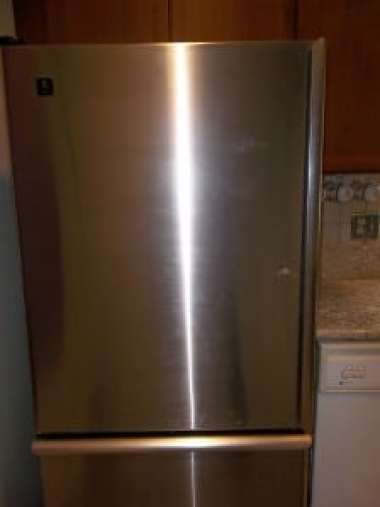 Stainless steel refrigerator with fingerprints all over it.