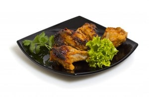 Broiled chicken on black plate.