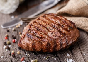 Delicious grilled beef steak on a wooden board with spices.
