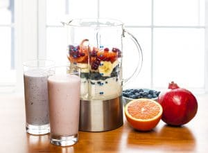 Prepared smoothies and healthy smoothie ingredients in blender with fresh fruit ready to blend on kitchen table