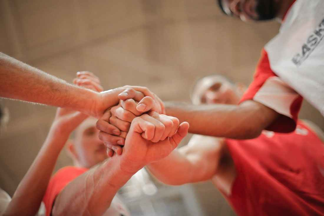 basketball team stacking hands together