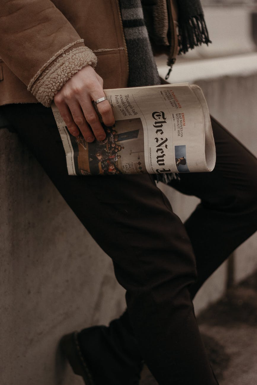 person in brown coat holding a news paper