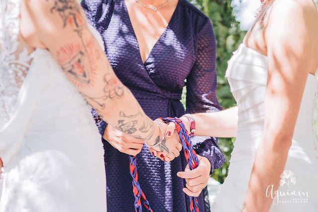 Handfasting of two lesbian brides by a wedding celebrant as a wedding ritual in a wedding ceremony in Portugal.