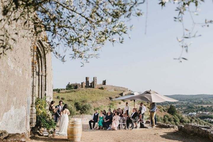To the left the bride and groom stand facing each other in front of their Alentejo wedding officiant while their 20 or so friends and family look on. Behind the couple is the facade of an old building with a beautiful arch and in the distance, an old castle.