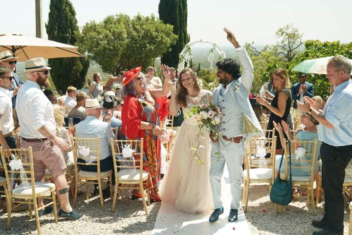 Scottish bride and Indian groom walk down the aisle as some guests stand and clap after their wedding ceremony conducted by their Algarve Wedding Officiant.