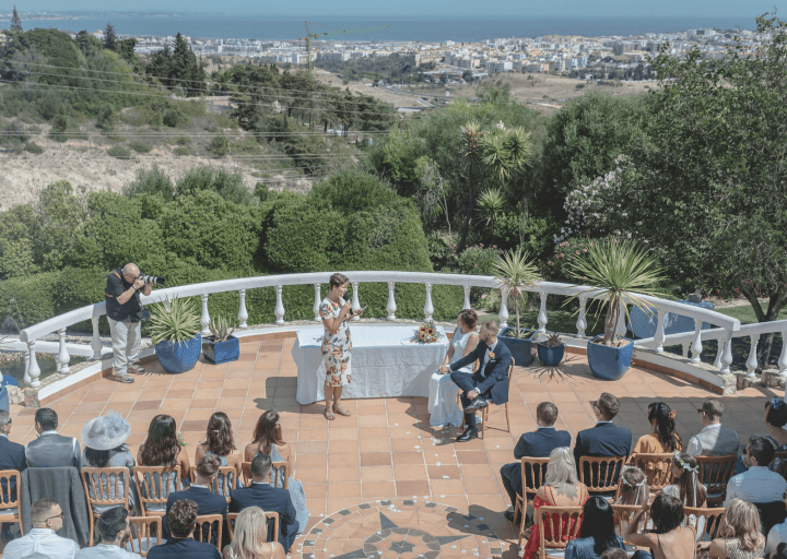 Your Algarve wedding officiant standing before the family and friends of the bride and groom who are seated to the left of the celebrant. Everyone is on a large terrace and all of Lagos and the Mediterranean Sea is the backdrop.