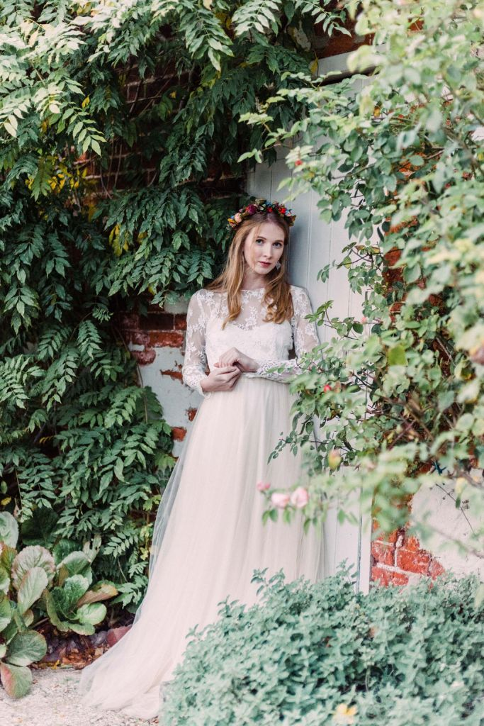 Bride against door in walled garden