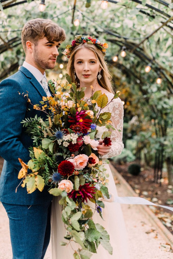 Close up of couple & bouquet under arch