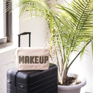 Pink make up bag with a black suitcase