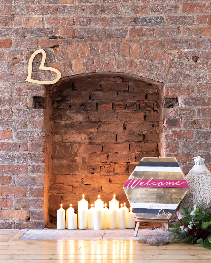 Brick fireplace styled with candles, gold heart and welcome to our wedding board