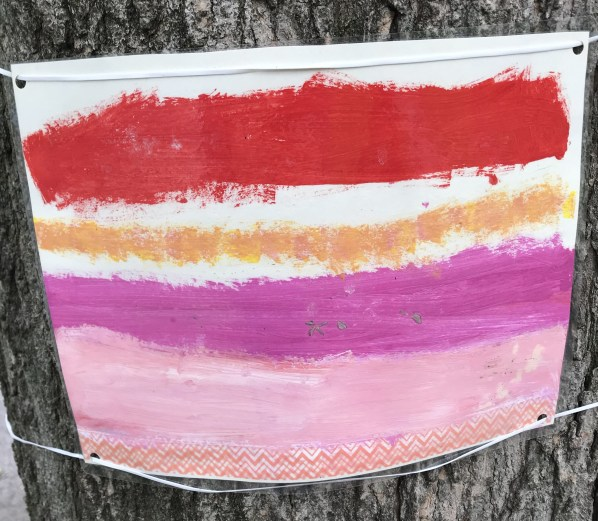A painting with red, orange, and pink stripes.