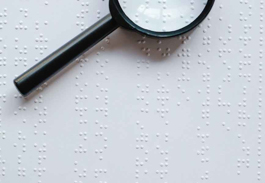 photo of magnifying glass on top of braille