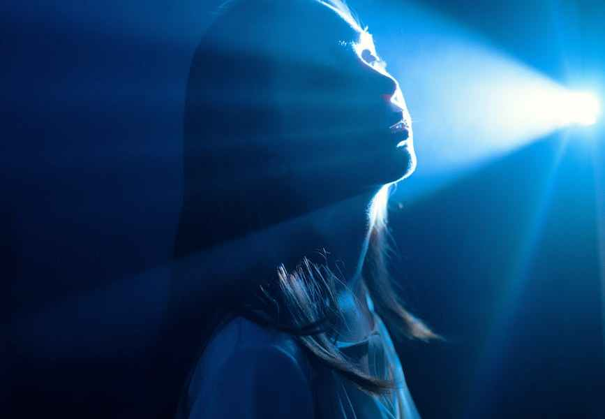 sensitive woman in shiny blue light ray