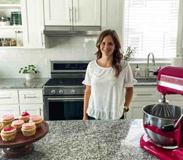 Alana in her kitchen with a mixer and almond cupcakes with strawberry frosting