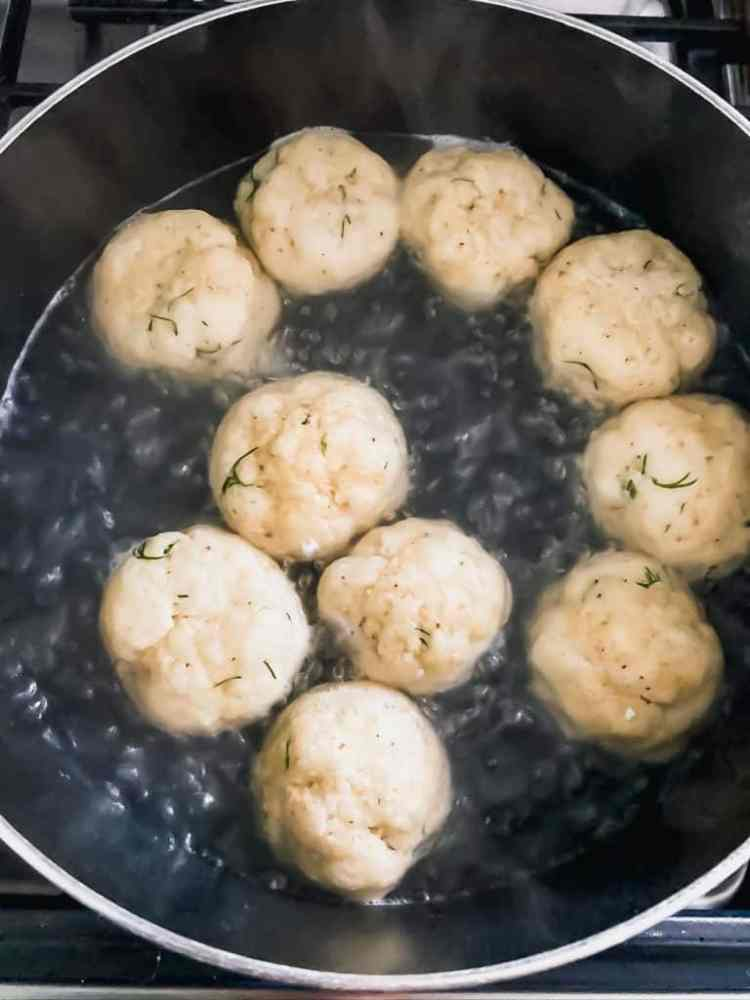 matzo balls in a black pot of boiling water