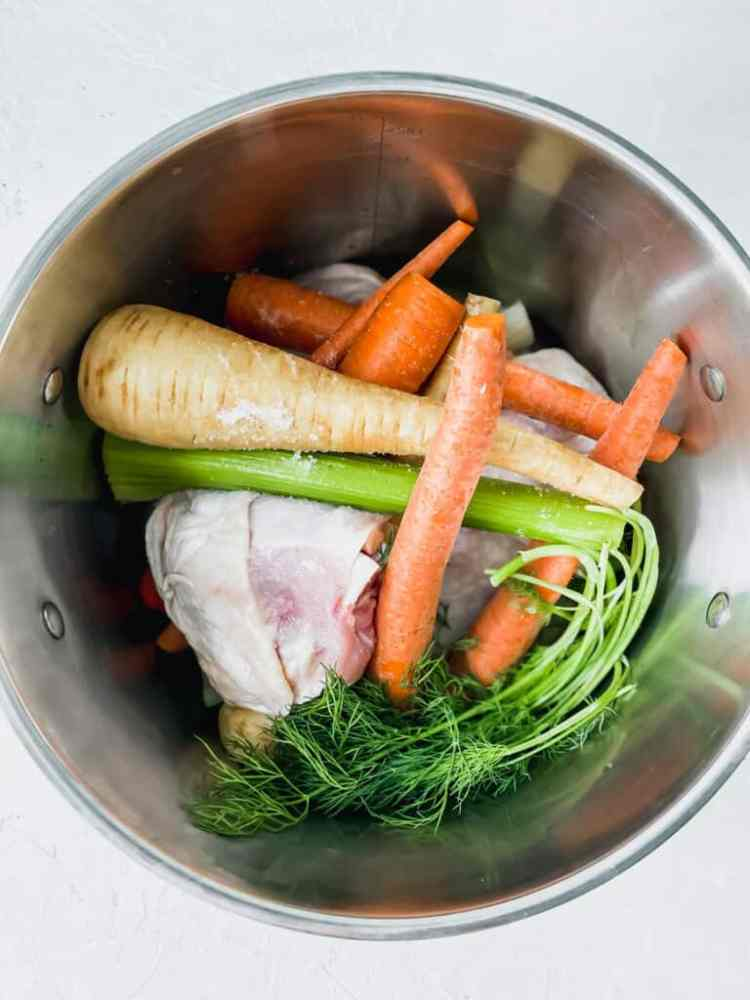 Chicken thighs, carrots, celery, onion, dill, and parsnips in a metal pot