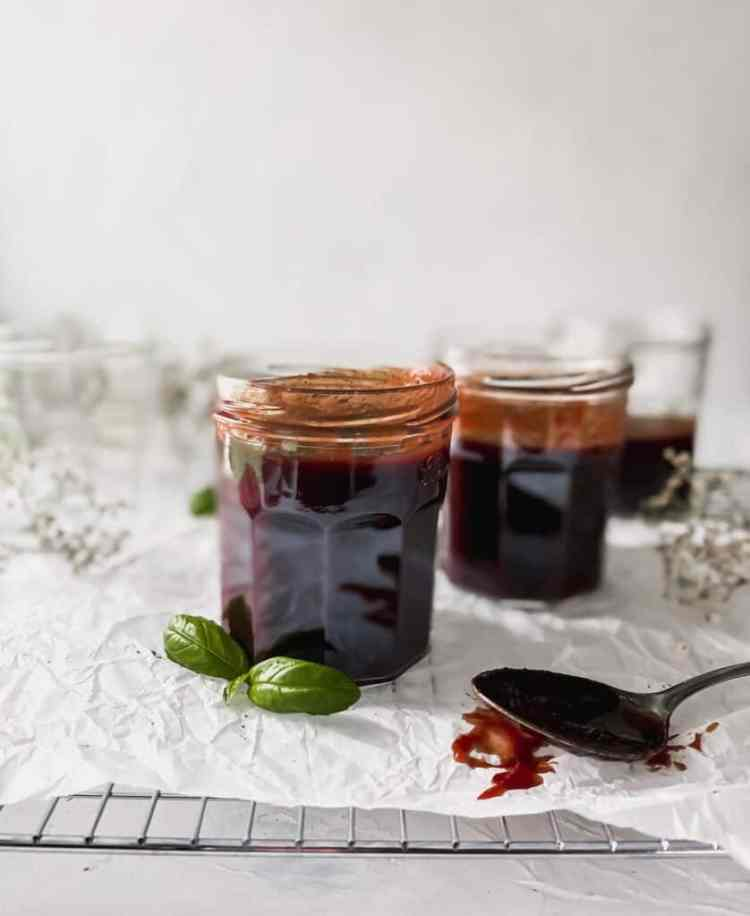 pomegranate bbq sauce in jars with a spoon covered in sauce