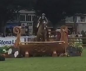 Chestnut horse jumping a fence that looks like a ship