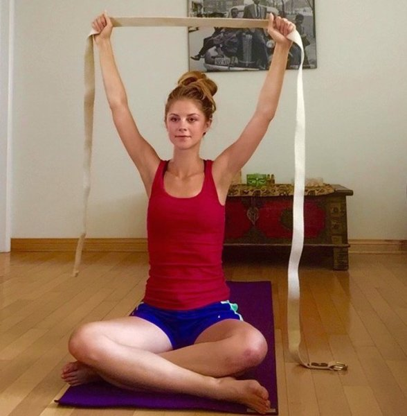 arms overhead with strap yoga for back pain