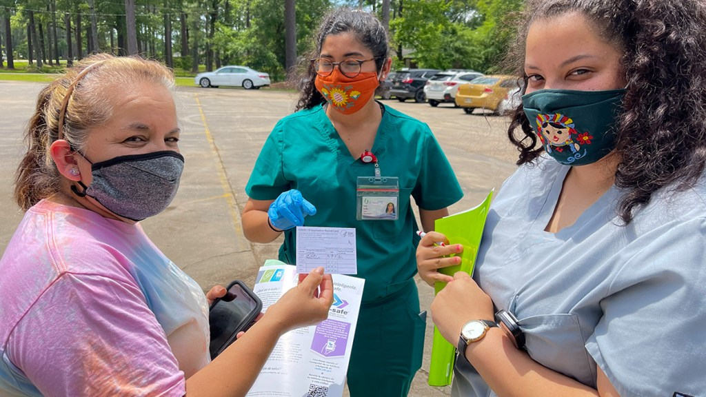 Woman proudly showing her vaccination card during a pop-up event in Forest, MS