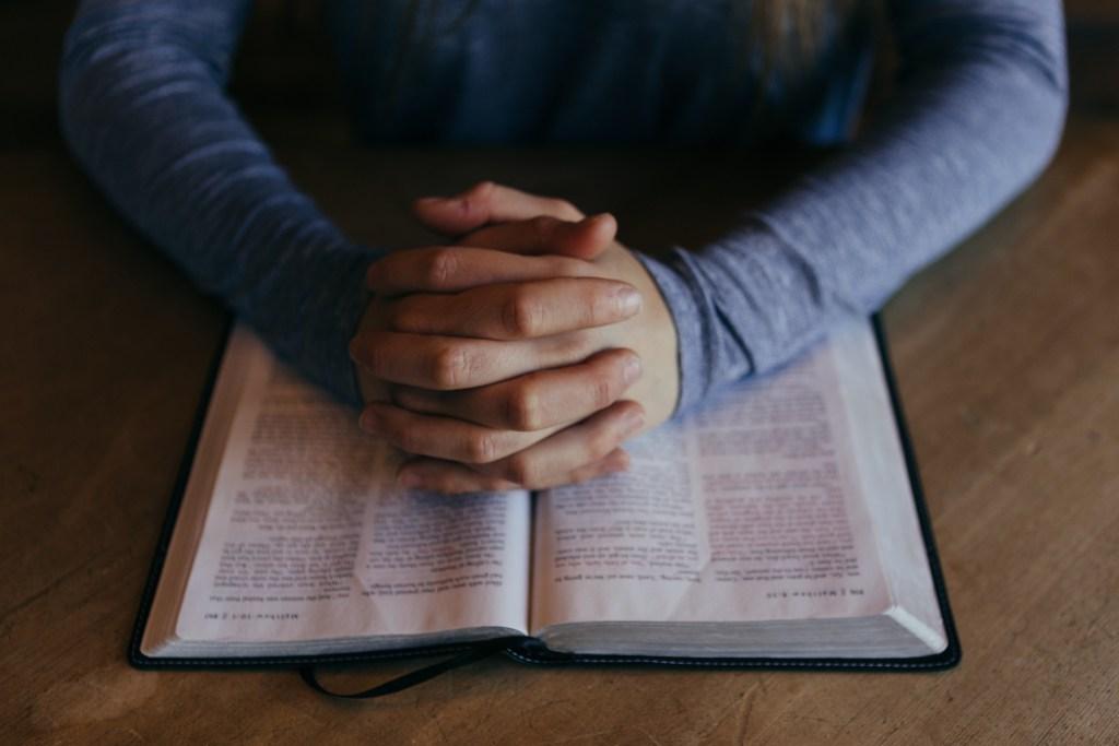 prayer-hands-folded-and-bible-unsplash