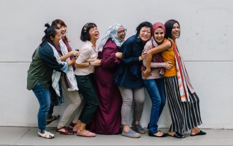 Line of women supporting each other laughing