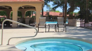 Large, round walk-in spa with sparkling blue water, patio seating and tables beside, pool behind - 945 N Pasadena, Mesa AZ - Park Centre Patio Homes - Bill Salvatore, Arizona Elite Properties 602-999-0952 - Arizona Real Estate