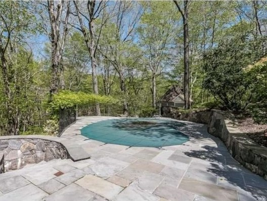 Round swimming pool surrounded by greenery for privacy, and gray stone patio and walkway (photo: RIS Media) - Cyndi Lauper's Stamford CT home for sale - Bill Salvatore, Arizona Elite Properties 602-999-0952 - Arizona Real Estate