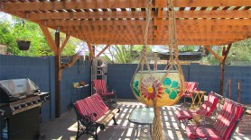 wrought-iron patio furniture with red and white cushons, barbecue grill and hanging plants covered by a large wood Pergola - Beautiful covered Patio - 161 N 88th Place, Mesa AZ - Bill Salvatore, Arizona Elite Properties - Homes for sale in Mesa AZ