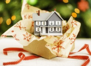 Small house sitting on wrapping paper and ribbon - Reasons to List a Home During the Holidays, Is Christmas a good time to sell a home - Bill Salvatore, Arizona Elite Properties 602-999-0952 - Home Selling Advice