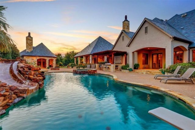view across sparkling blue pool to patio and back of home with varied rooflines - Selena Gomez's Fort Worth Texas Home for Sale - Bill Salvatore, Arizona Elite Properties 602-999-0952 - Arizona Real E