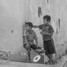 Image of teamwork and vision omani boys selling pomegranate fuits on a street corner