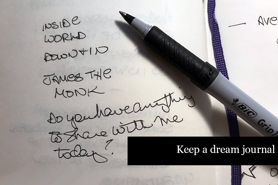 """Close up of open  journal with pen and scribbled notes Text says """"Keep a dream journal"""""""