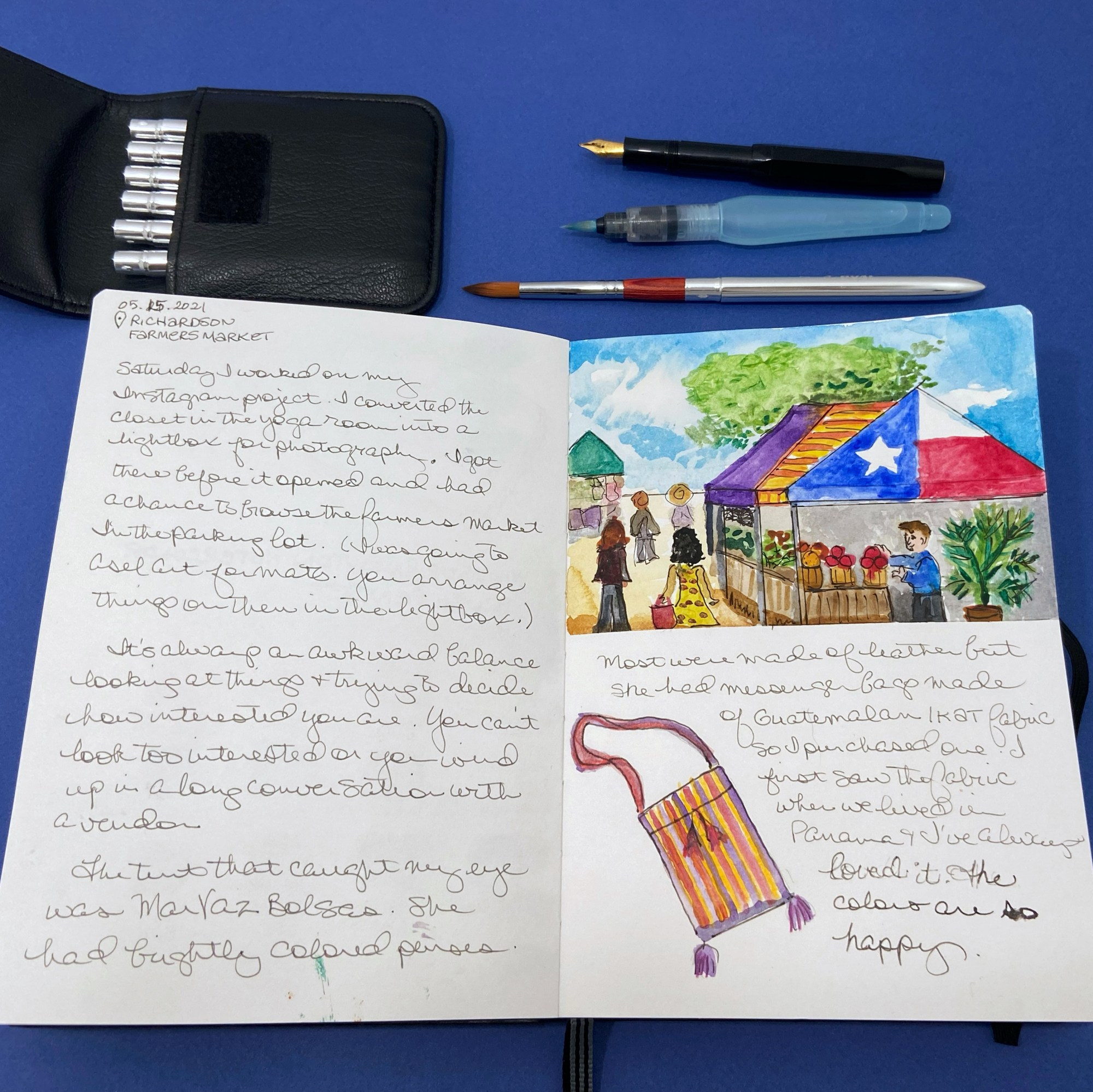 Open journal pages with travel watercolor tools. There is an illustration of an open air market, sketch of a purse, and handwriting with a fountain pen. Image by Cathy Hutchison