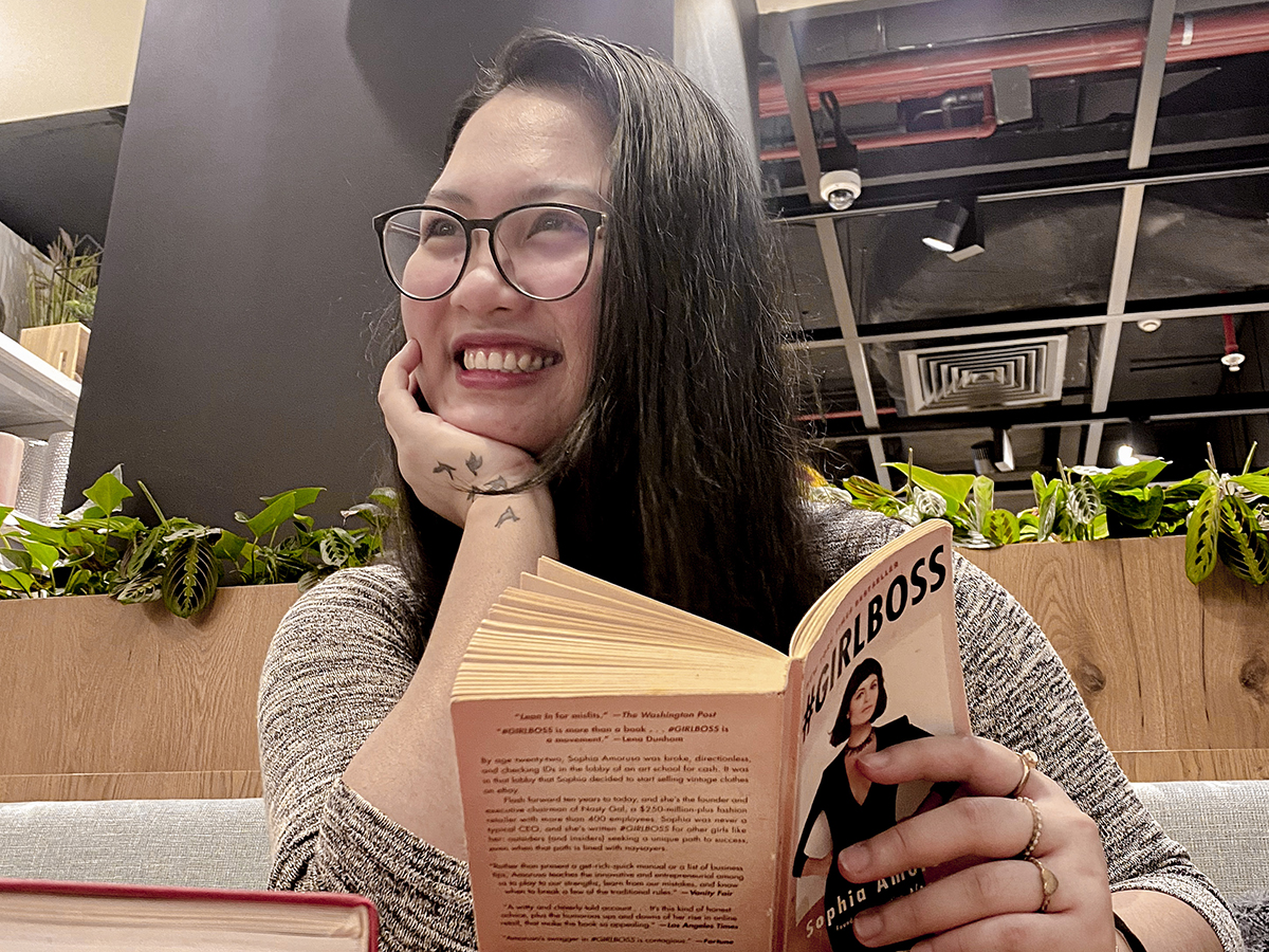 Renee Alexis reading a book with a journal beside her.
