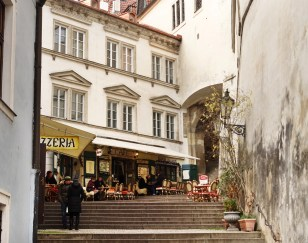 """I love this, told to me by the awesome guide that took me all over the back alleys of Prague and away from all the tourist stops and Segways. """"Take me away from people, please."""" Anyhow, he laughed when we walked by this place, right below the castle, and told me this story: This quiet corner is the single worst-reviewed restaurant in all of Prague. They're known for fleecing tourists, serving horrible food, mean service, bad health scores and lighting up TripAdvisor, with matches, for years. So then what did they do? They just painted over the restaurant name and address. Nothing but generic signs like """"pizza"""" and """"cafe"""" so now nobody can look up the reviews, or write about them... nobody could find them! They just sit and wait for the next moth to trip down the steps and into their web."""