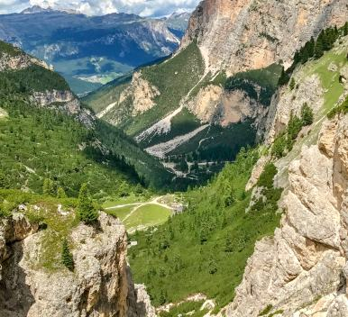 Down THERE is where I'm going to take you next. Can you see it? Zoom in. It's what everyone says is the rifugio with the best food in the Dolomites. Tucked into this little valley in the middle of nowhere, surrounded by towering peaks on all sides. You can't drive there. It's a steep two hour walk up to it, or down to it, as I have done. Another 30 minutes of zigzags down from right here. They are known for their wood-fired cooking and you can smell the wafts of woodsmoke and grilled meat all the way up here.