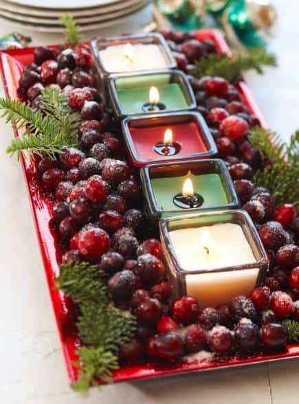 cranberries and pine sprigs surround votive candles