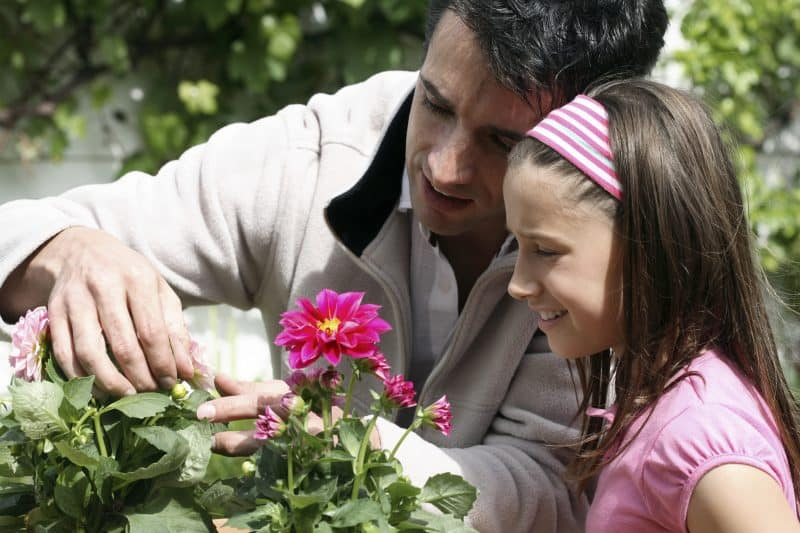 Father showing daughter how to prune flowers and grow garden
