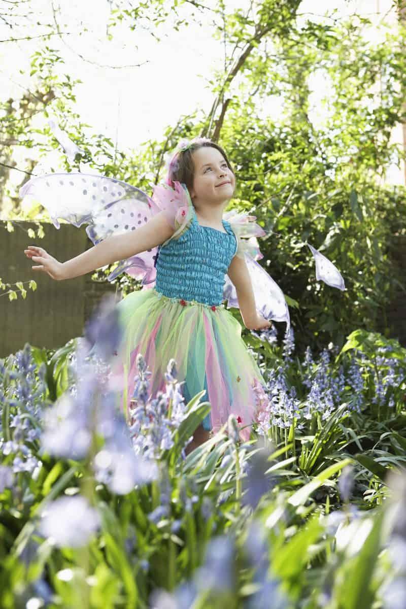 Gardening activities for preschoolers - girl dancing in garden in a fairy costume.