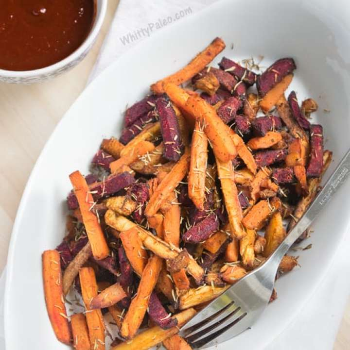 Colorful fries from carrots and beets on a white plate with bbq dipping sauce.