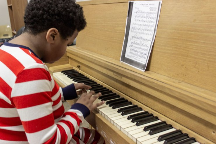 One Youth Art Team artists noodling around on the piano.