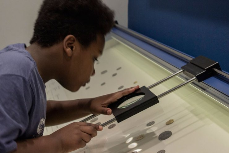 One Youth Art Team artists looking at ancient Greek and Roman coins under a magnifying glass.