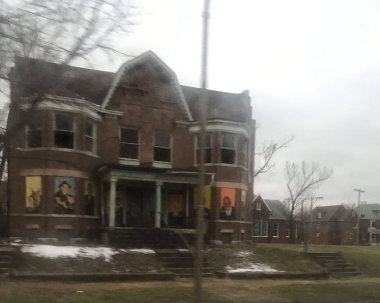 Vacant apartment building with painted portraits of community leaders attached to the windows.