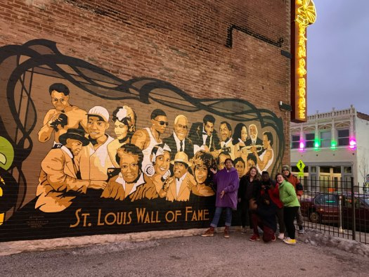 Six Youth Art Team artists posing in front of the St. Louis Wall of Fame mural that depicts 18 prominent African American people from St. Louis.