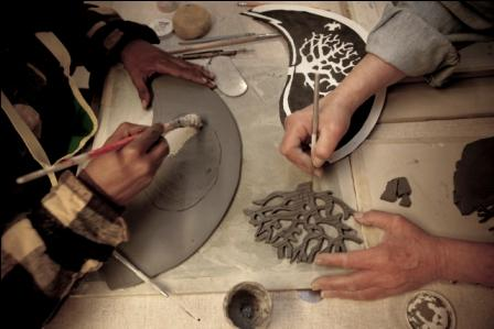 Two hands working with clay to create tiles