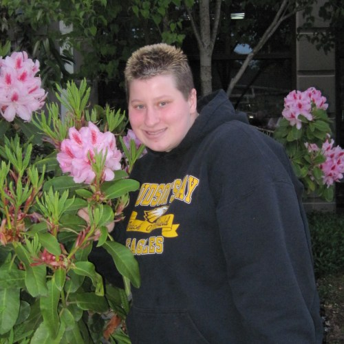 Picture of Cassy smiling by pink flowers