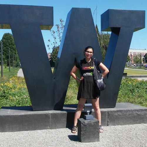 Thalia standing in front of a big letter W at the University of Washington