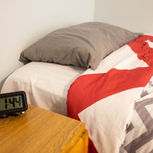 Bed with alarm clock on nightstand