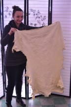 Annie, Catholic Charities' SNAP Outreach and Education Specialist, holding the deer skin